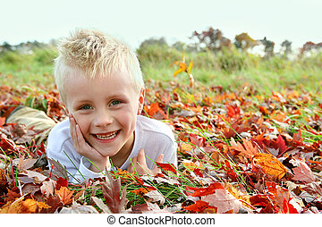 Portrait of Happy Young Child Laying in Fallen Autumn Leaves