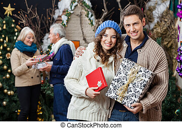 Portrait of happy young couple holding Christmas presents with parents standing in background at store