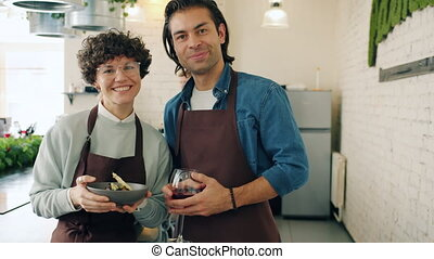 Portrait of happy young couple in aprons smiling in cooking ...