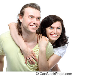 Portrait of happy young couple in love looking to side, she embraced boyfriend's shoulders from back