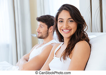 Portrait of happy young couple on bed at home - Upset woman...