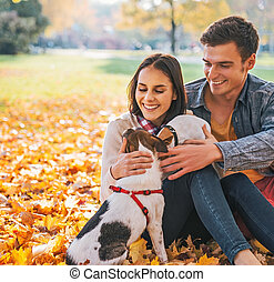 Portrait of happy young couple sitting outdoors in autumn park a