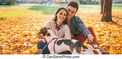 Portrait of happy young couple sitting outdoors in autumn...
