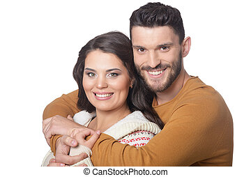 Portrait of happy young couple smiling and hugging