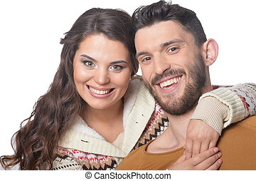 Portrait of happy young couple smiling and hugging on white background