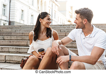 Portrait of happy young couple smiling and talking together while sitting on stairs outdoors with paper cup