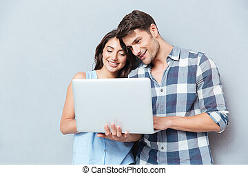 Portrait of happy young couple using laptop over gray background