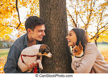 Portrait of happy young couple with dogs outdoors in autumn park