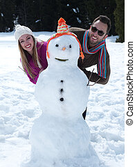 portrait of happy young couple with snowman