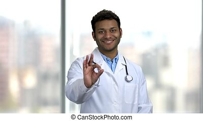Portrait of happy young doctor showing ok sign. Handsome Indian doctor in white coat looking at camera with a smile.