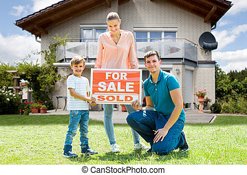 Family With A Sale Sign Outside Their Home
