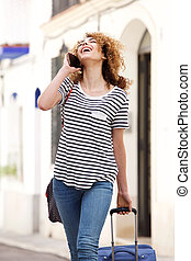 happy young female traveler walking and talking on mobile phone