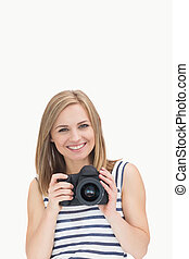 Portrait of happy young female with photographic camera