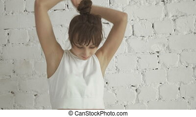Portrait of Happy Young Fitness Woman Dancing On White Brick Wall Background