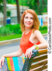 portrait of happy young girl sitting on a park bench