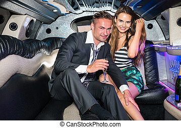 Portrait of happy young glamorous couple with champagne flute in limousine