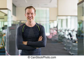 Portrait of happy young handsome man smiling with arms crossed at the gym during covid-19