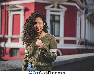 Portrait of happy young hispanic woman with beautiful curly hair in the street. Mixed race girl smiling. autumn season. Fall colors, red architecture european building