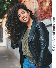 Portrait of happy young latino woman with beautiful curly hair in leather jacket and jeans standing in the street. Hispanic girl smiling. autumn season. Fall colors, park
