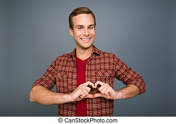 Portrait of happy young man making heart with fingers