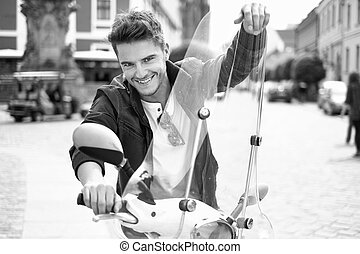 Portrait of happy young man riding a scooter