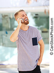 happy young man with beard talking on mobile phone