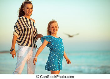 Portrait of happy young mother and child on beach in evening