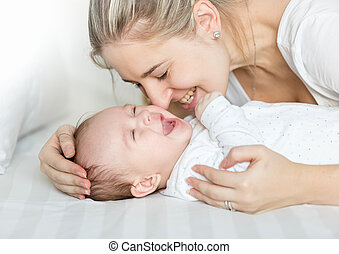 Portrait of happy young mother kissing her baby boy on bed