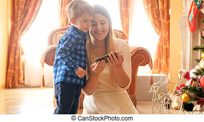 Portrait of happy young mother watching video on smartphone with her little son next to Christmas tree