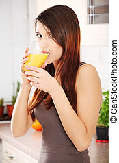 Portrait of happy young smiling woman drinking fresh orange juice