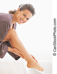 Portrait of happy young woman checking leg skin softness in bathroom