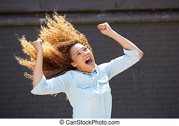 happy young woman cheering with arms raised