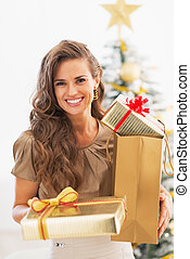Portrait of happy young woman christmas present boxes in...