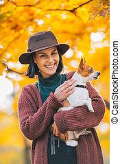 Portrait of happy young woman dog outdoors in autumn