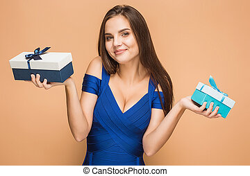 Portrait of happy young woman holding a gifts on brown -...