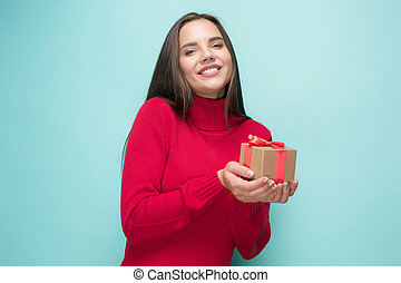 Portrait of happy young woman holding a gift isolated on...