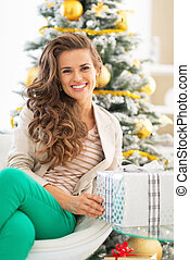 Portrait of happy young woman holding christmas present box