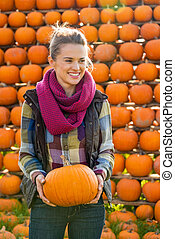 Portrait of happy young woman holding pumpkin