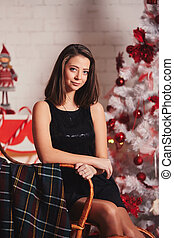 Portrait of happy young woman in black dress in a rocking chair and relaxing near christmas tree