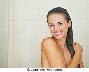 Portrait of happy young woman in shower
