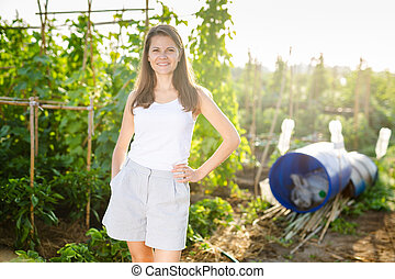 Portrait of happy young woman in summer garden on day