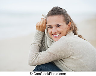 Portrait of happy young woman in sweater sitting on lonely beach