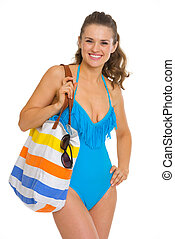 Portrait of happy young woman in swimsuit and beach bag