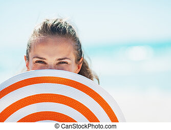 Portrait of happy young woman in swimsuit hiding behind...