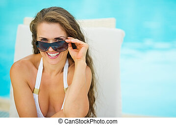 Portrait of happy young woman in swimsuit relaxing on chaise-lounge