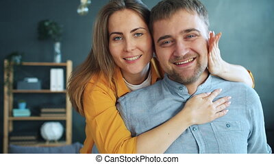 Portrait of happy young woman kissing and hugging husband at home looking at camera