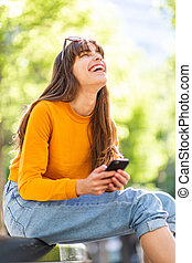 happy young woman laughing with cellphone in park