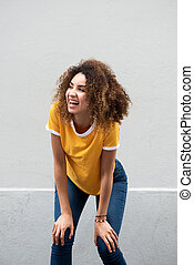 happy young woman laughing with hands on knees
