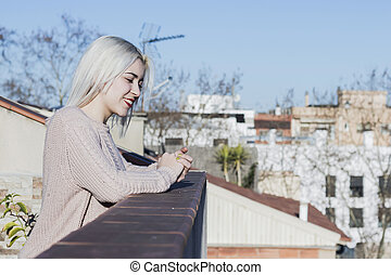 portrait of happy young woman on balcony looking away