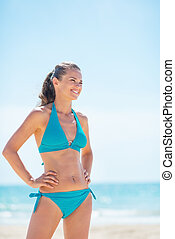 Portrait of happy young woman on beach looking on copy space